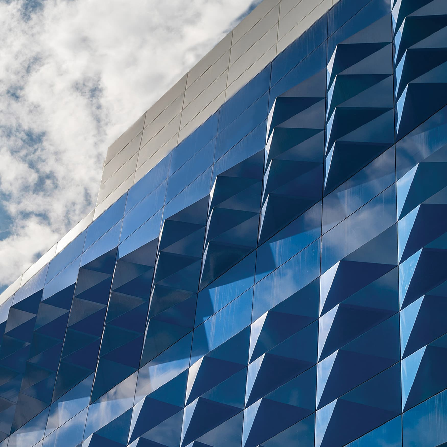 Geometric building facade design in reflective blue with clouds in the sky