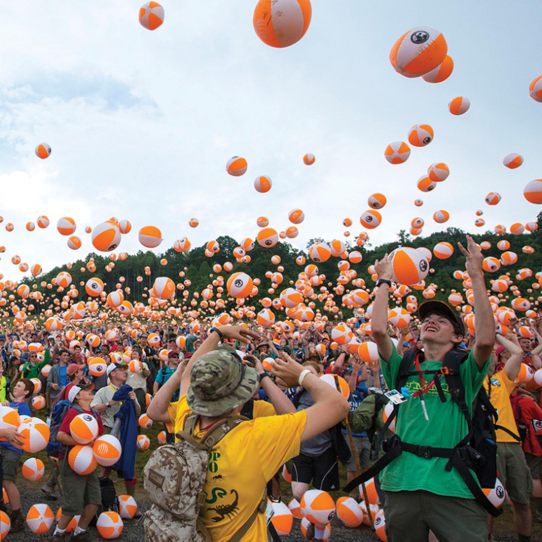 Boy Scouts at an outdoor camp throwing beach balls into the sky.