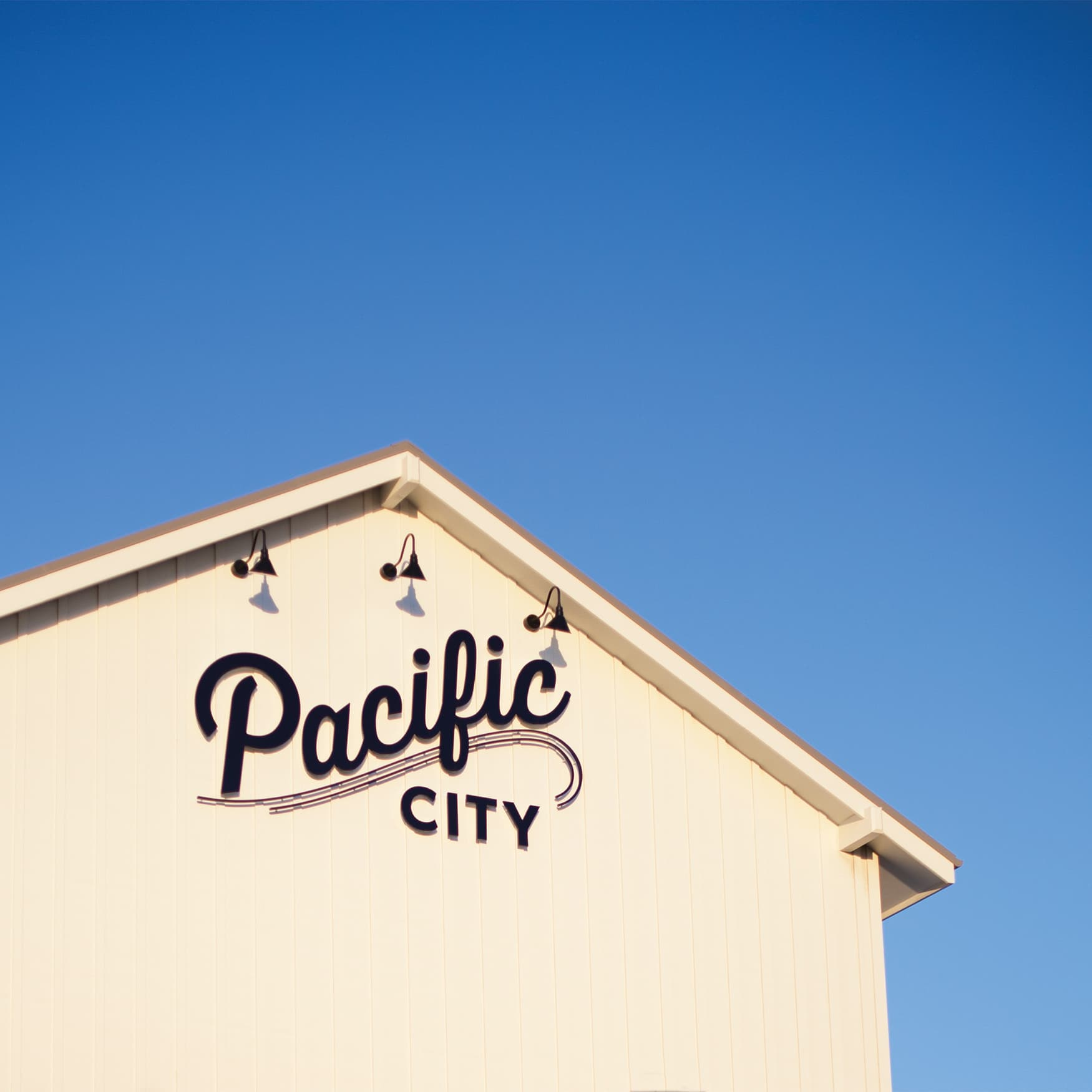 Pacific City branded signage on project building contrasts against the blue sky.