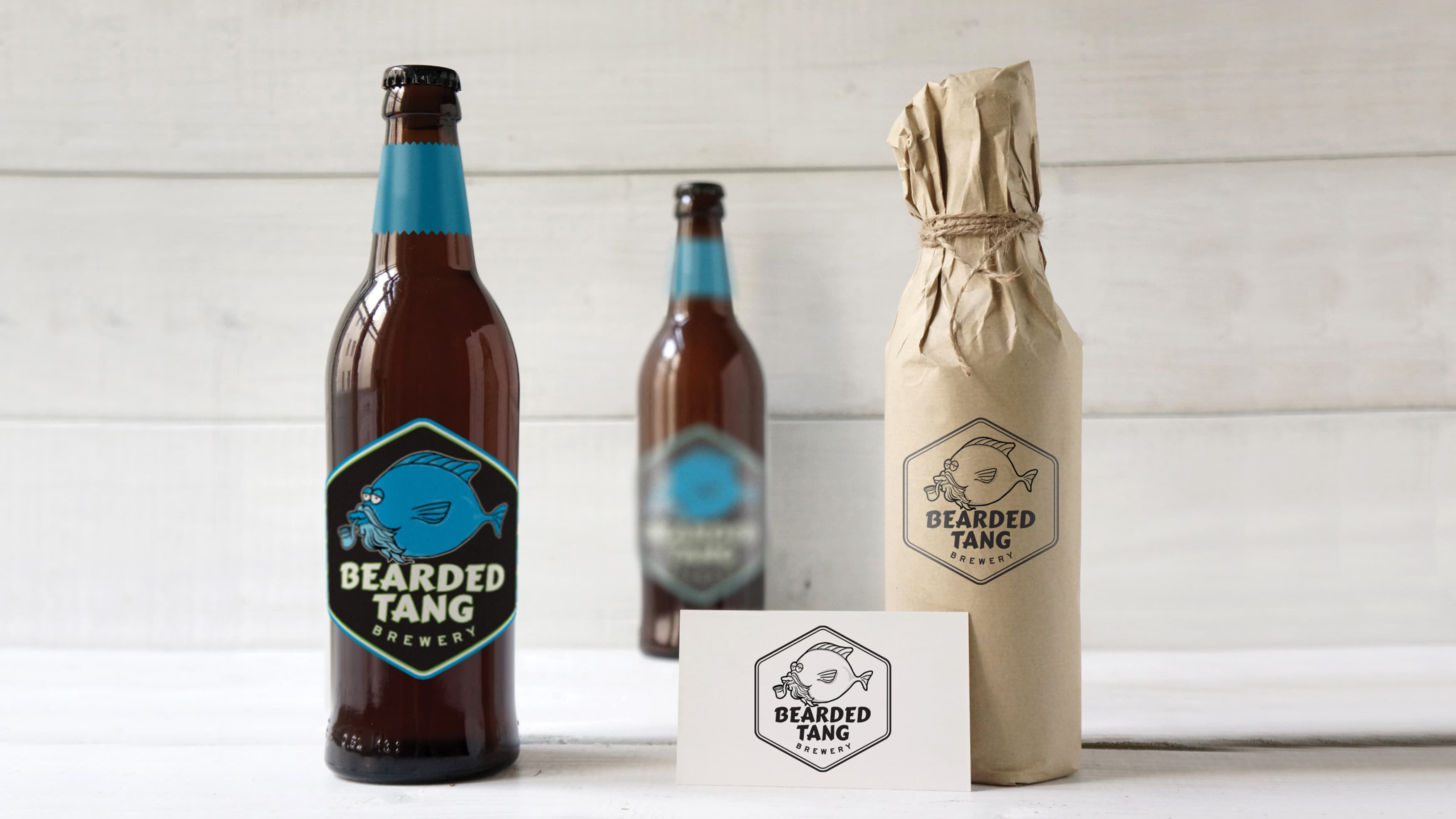 Beer bottles with custom logos on them set up against a white background.