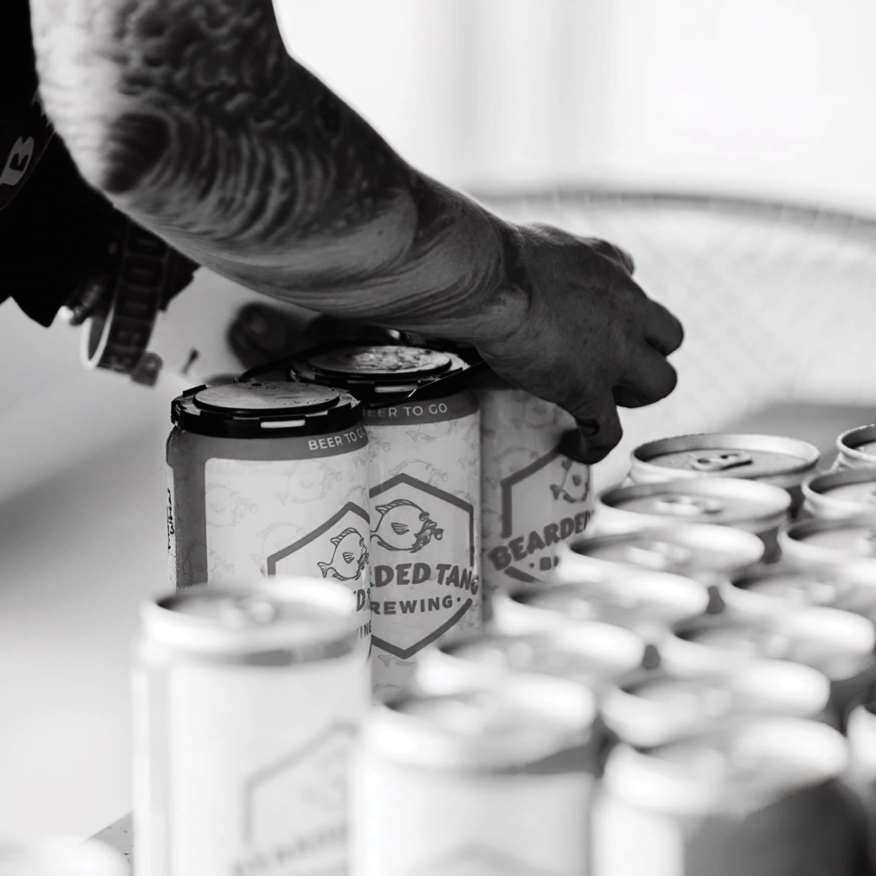 Person putting down a case of beer cans with custom designed label wraps.