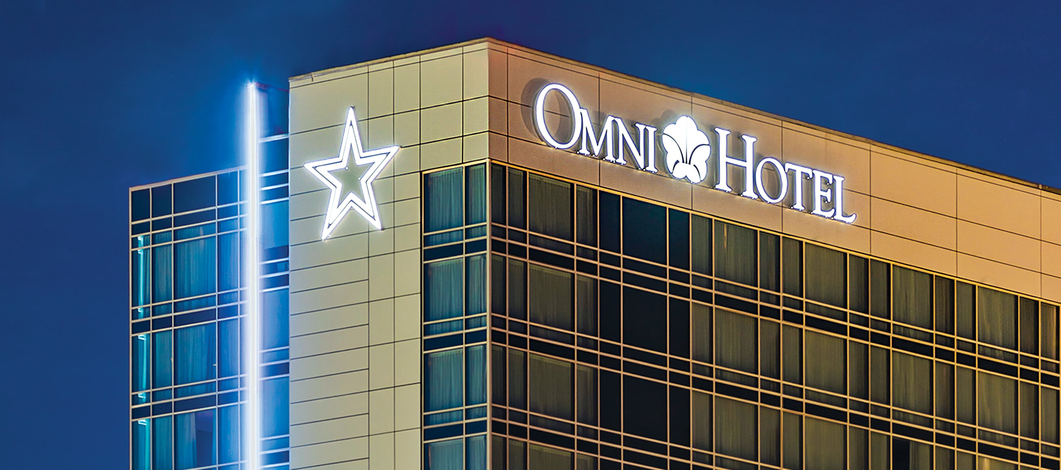 Illuminated hotel sign at dusk for Omni Hotel near Dallas.