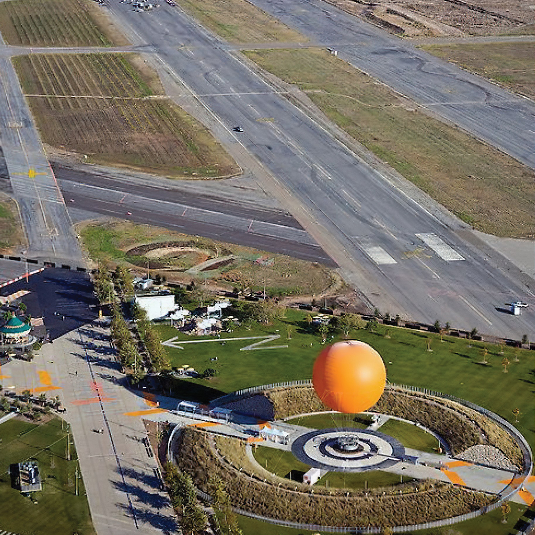 Aerial Shot of Great Parks and Runway with Orange Hot Air Balloon.
