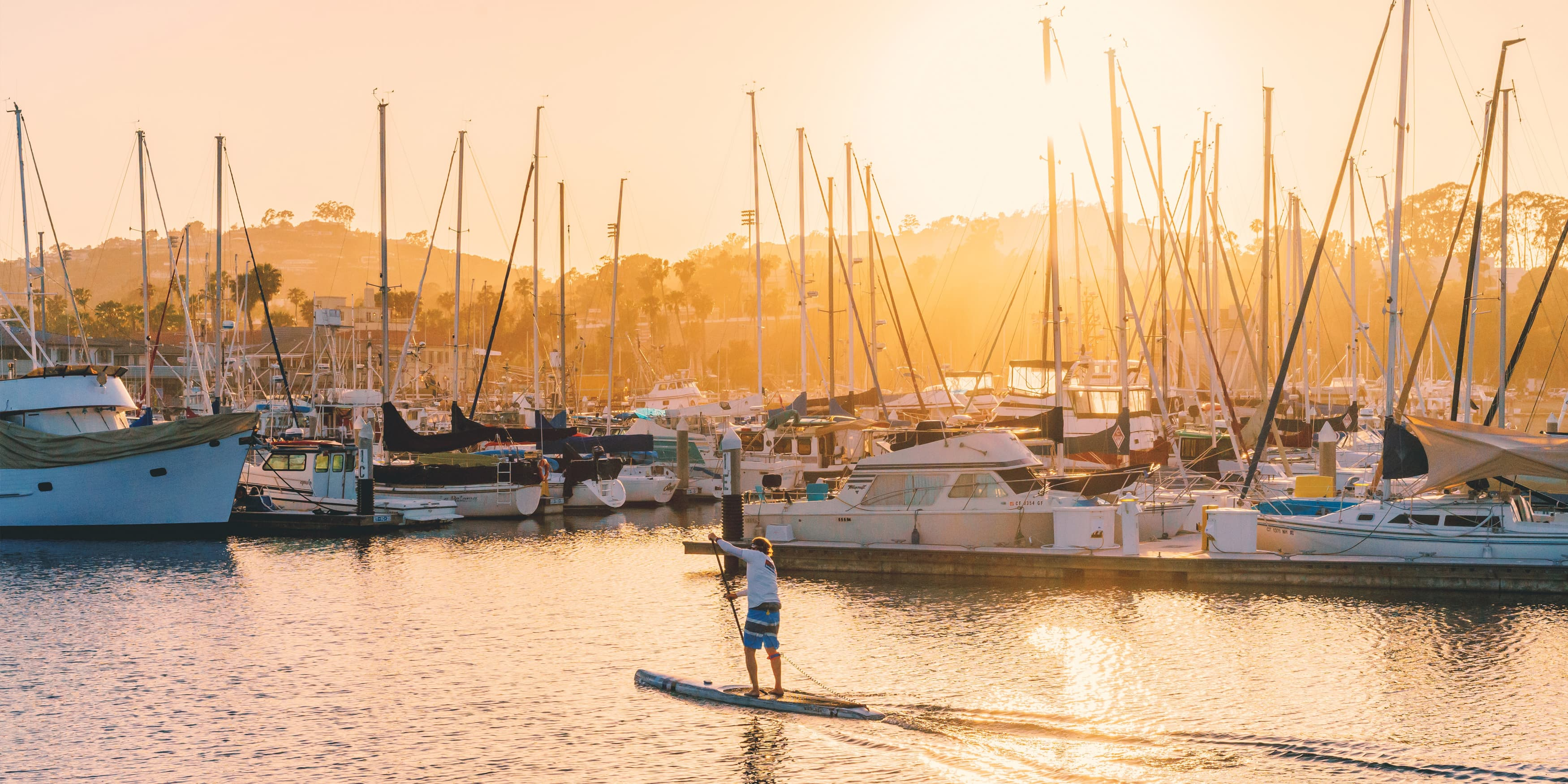 The City of Dana Point, man paddle-boards at sunset in the Dana Point Harbor