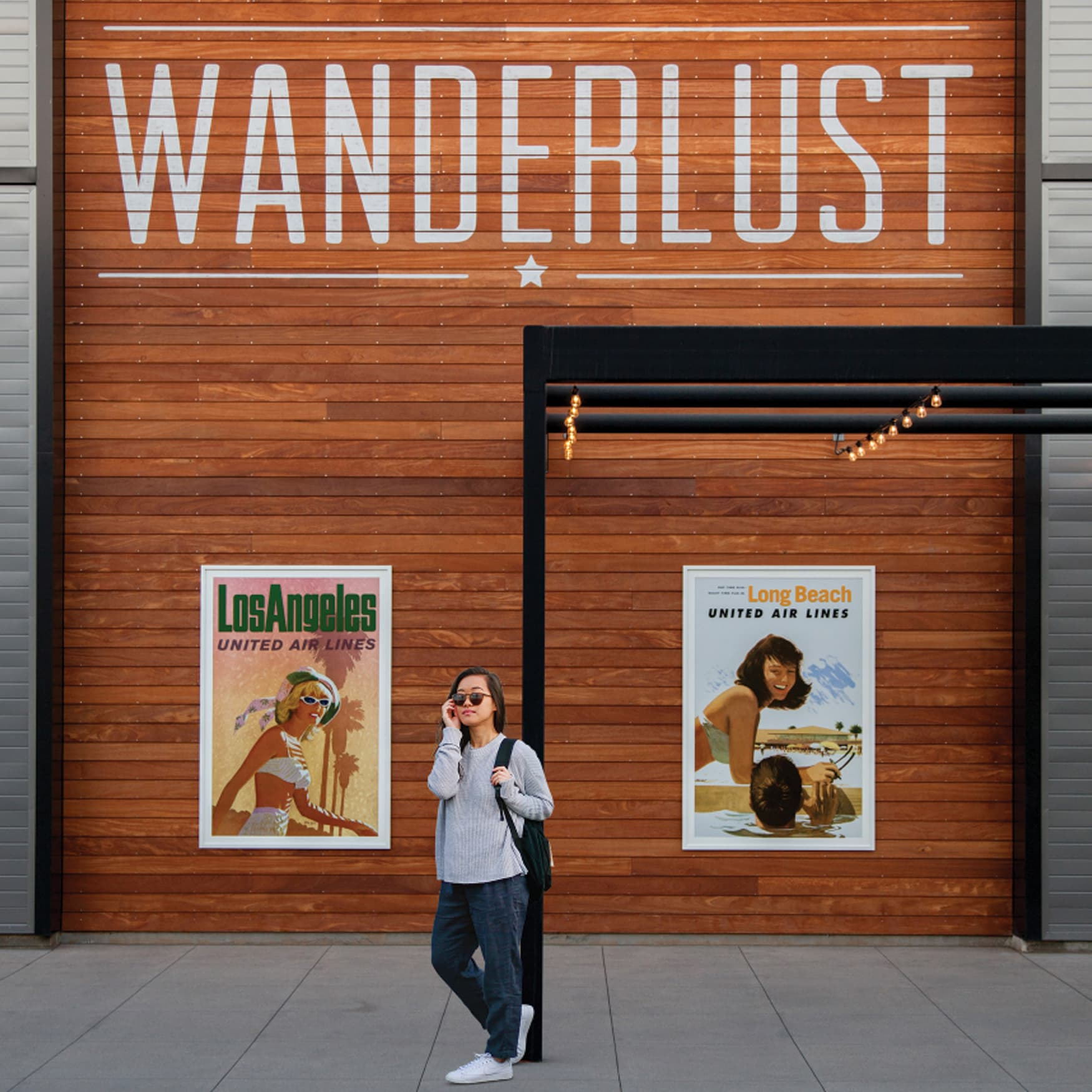 Girl standing in front a wall with art posters and the word WANDERLUST painted on it.