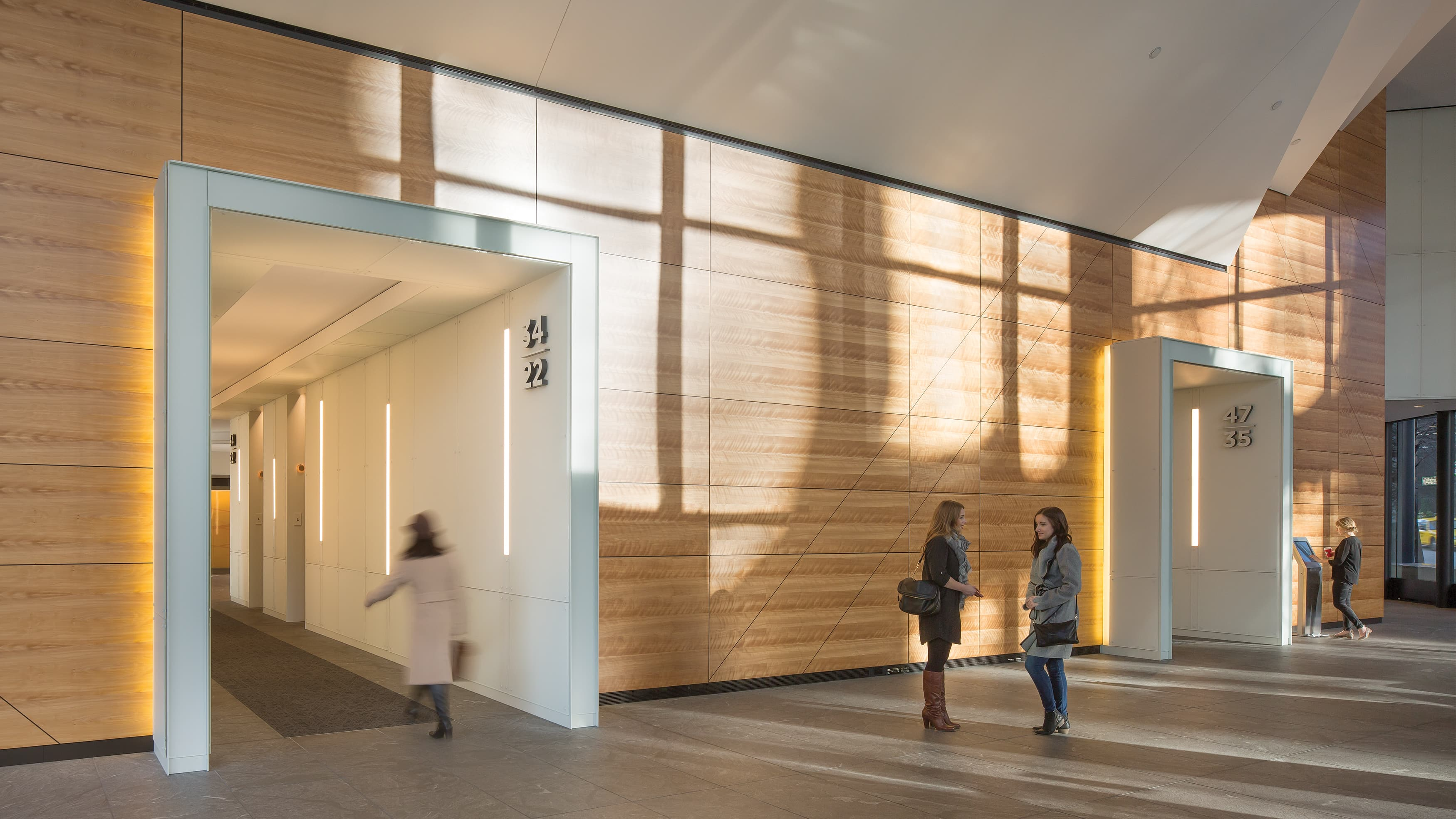 Wood wall in interior of modern office building with people walking through.