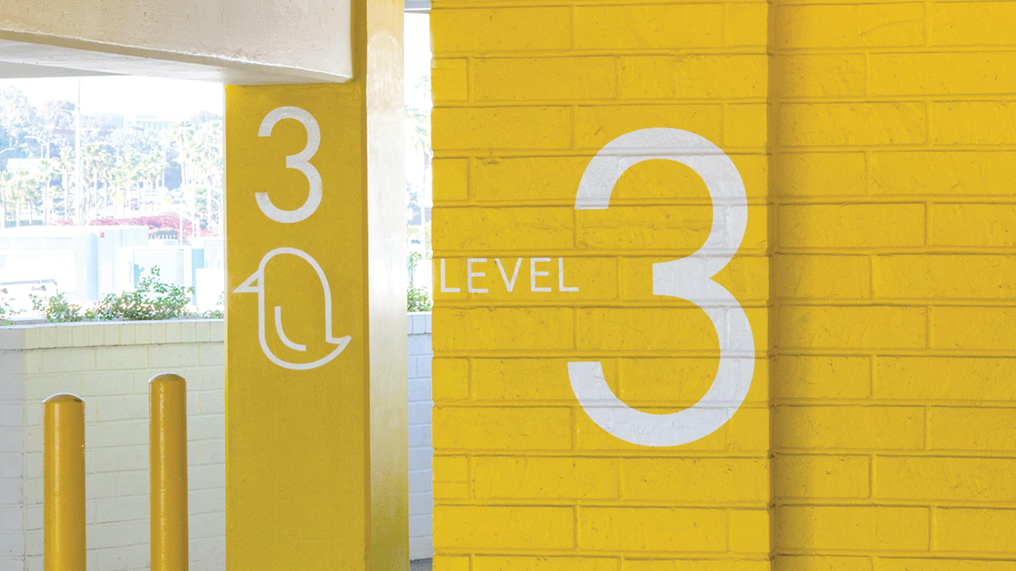 Yellow painted parking garage graphics on brick wall at Lido Marina Village