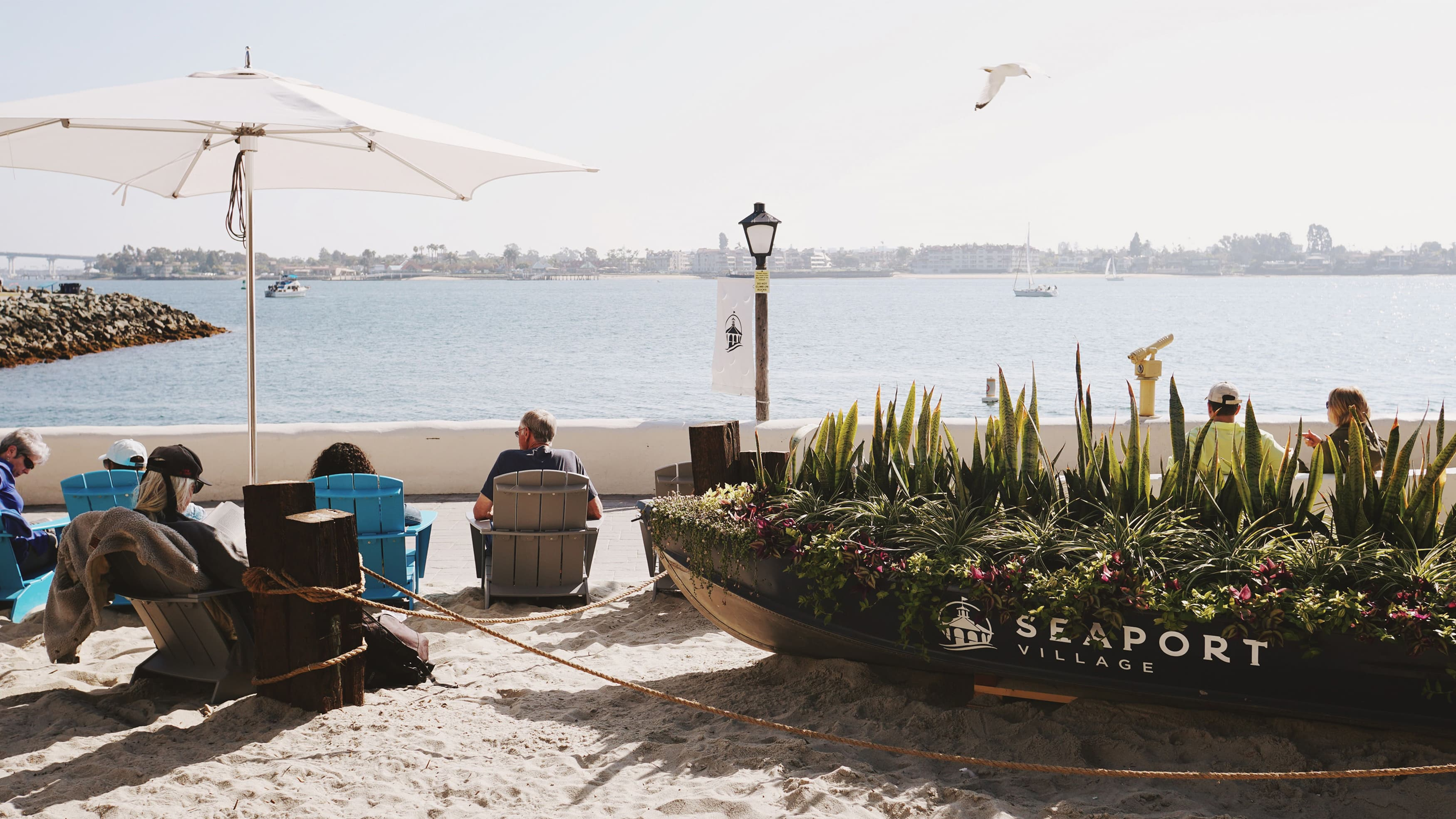 Man overlooks the Port of San Diego from the Seaport Village boardwalk.
