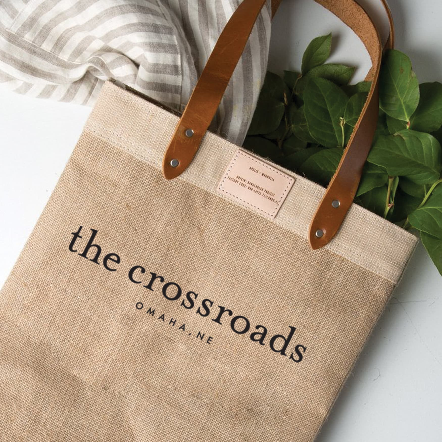 Tote bag with brand logo The Crossroads printed on it and a some plants and a linen cloth falling out of the top.