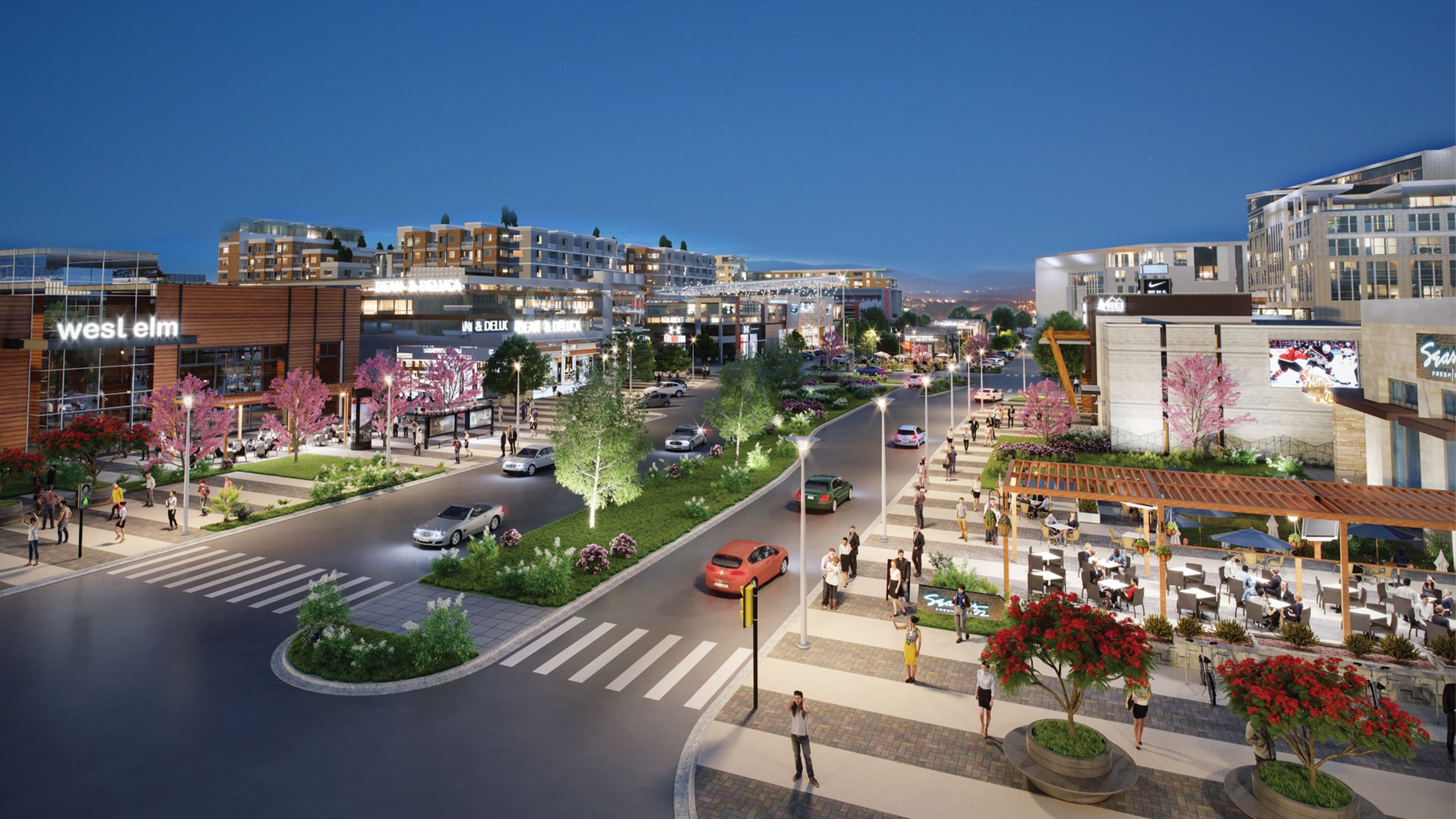 Evening view of a mixed-use and retail development with shopping, dining, and people walking around outdoors.