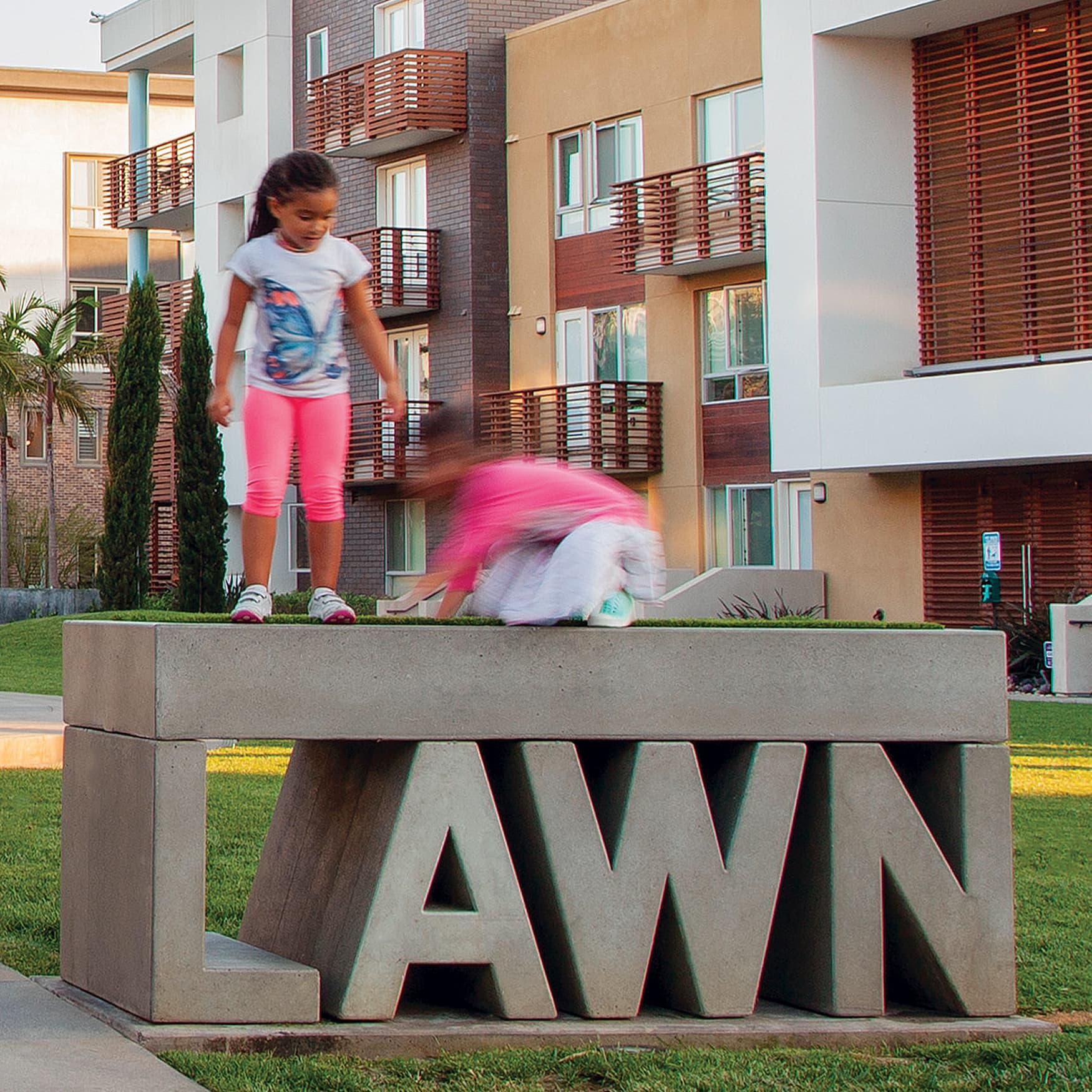 Two young girls playing on a concrete sign at the park.