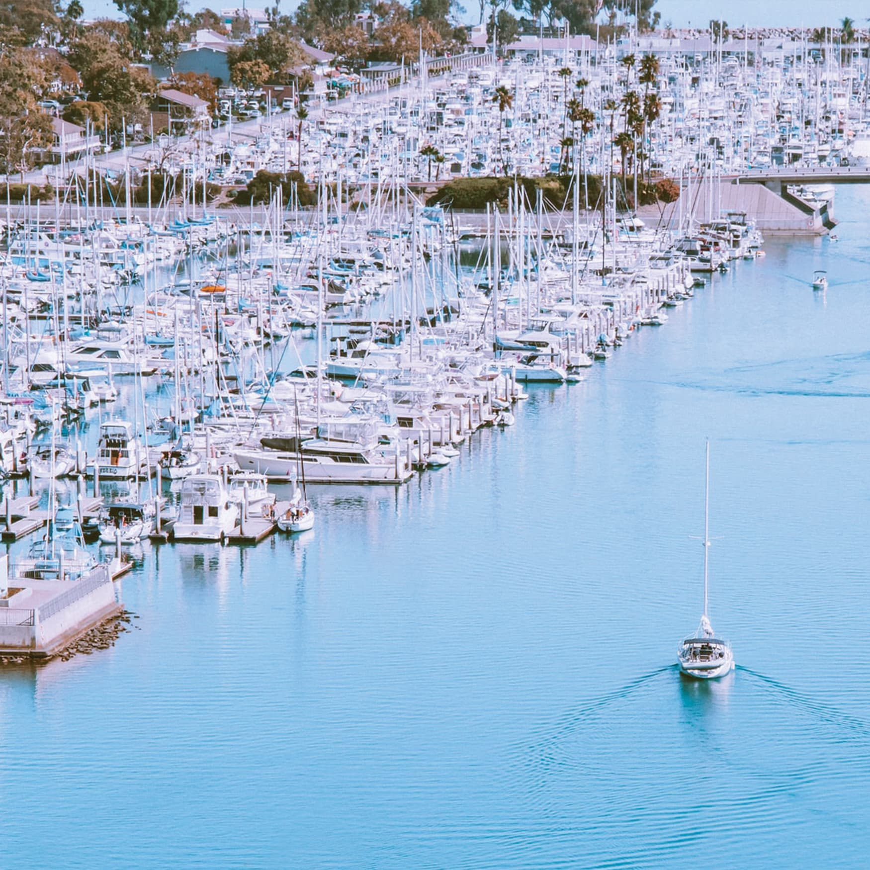 A boat sailing through the main lane at Dana Point Harbor with the current waterfront retail and restaurants in the background.