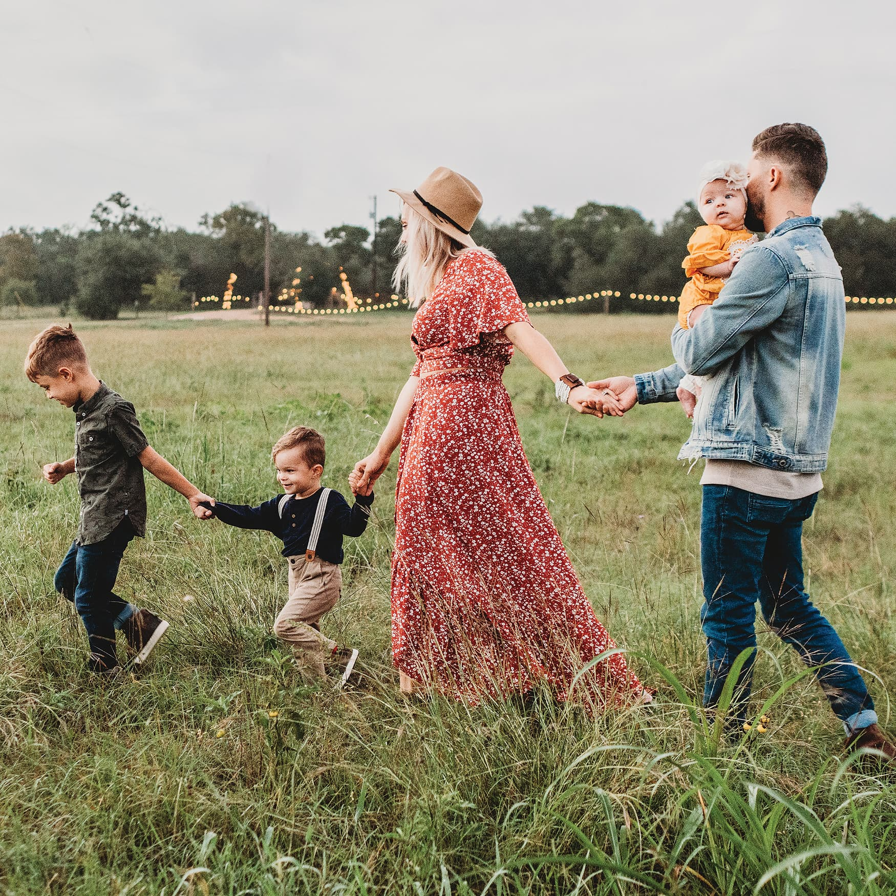 Family with children walking through a grass field on a farm.