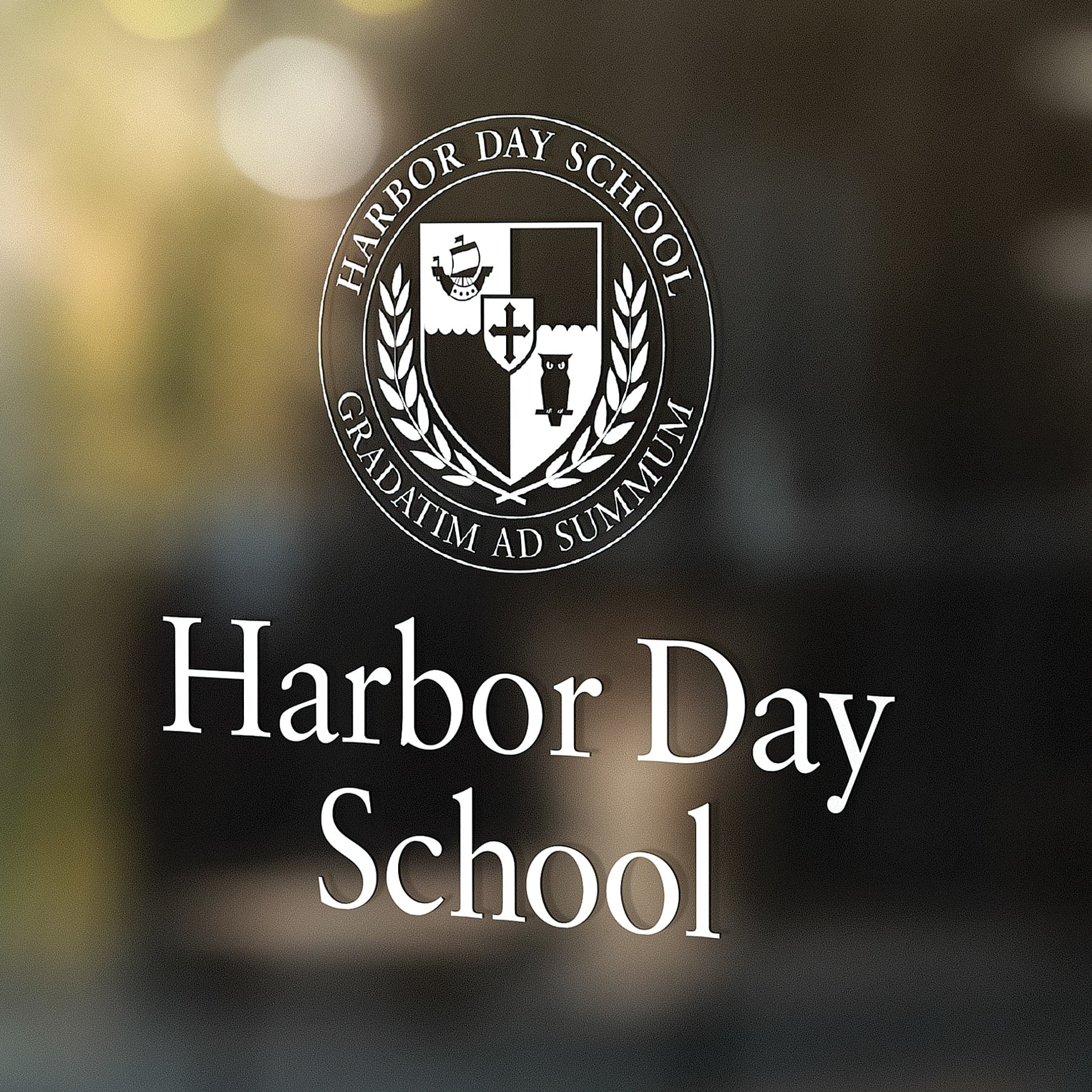 Harbor Day School logo printed on a glass reflective window.