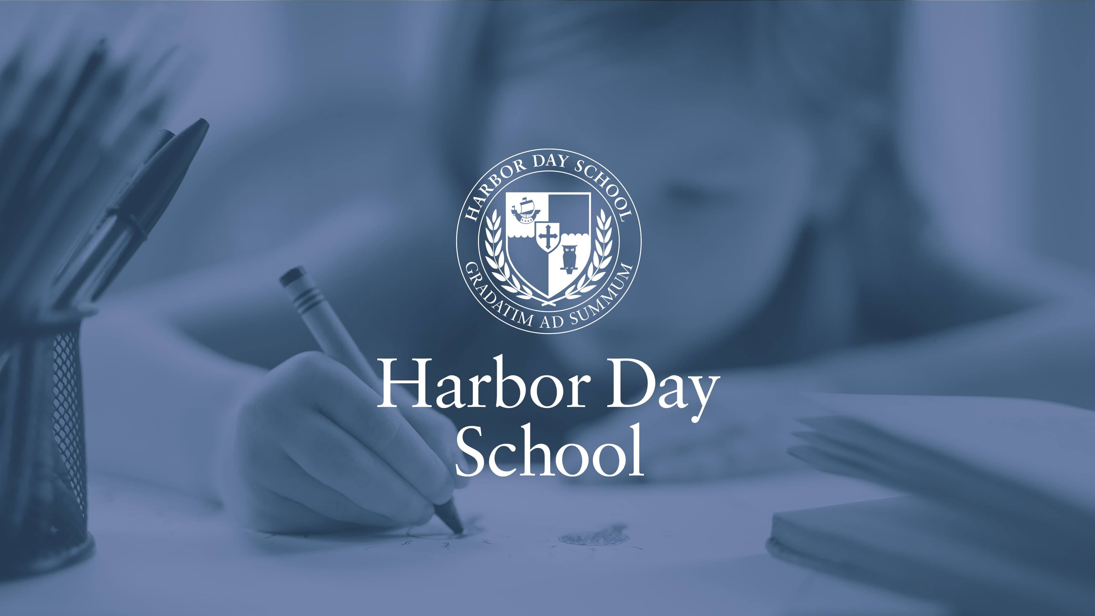 Harbor Day logo on an image of a young girl drawing at school.