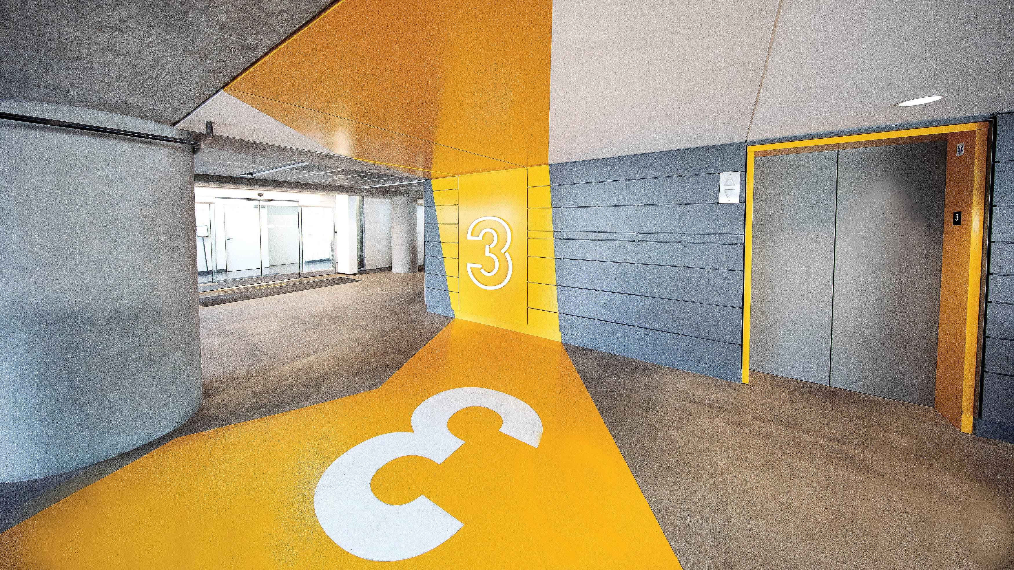 Yellow Painted Parking Garage with Level Numbers.
