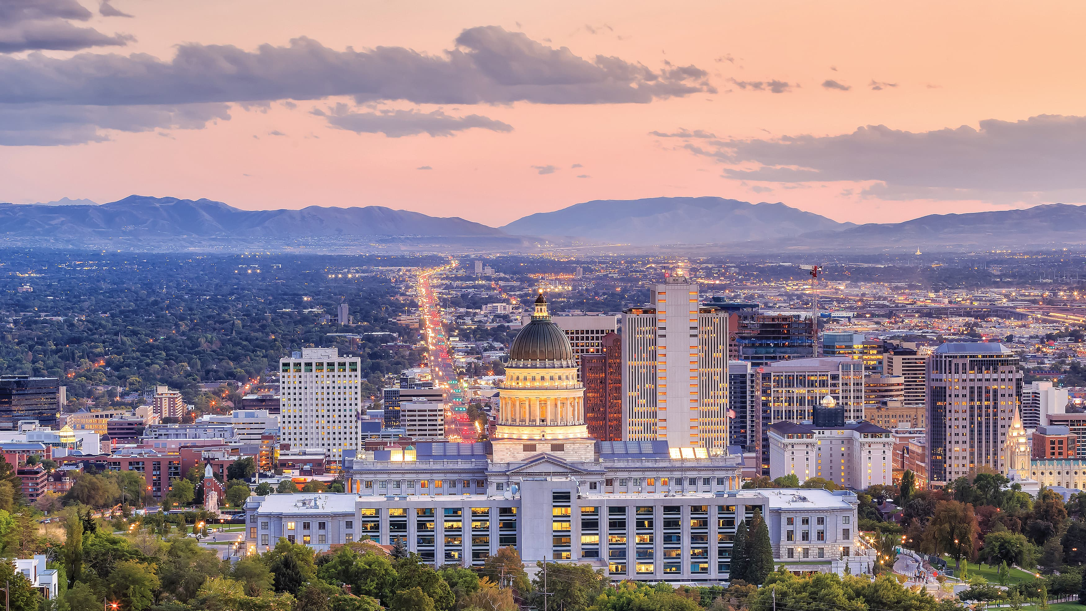 Aerial city evening view of Salt Lake City, Utah with the sun setting in the background.
