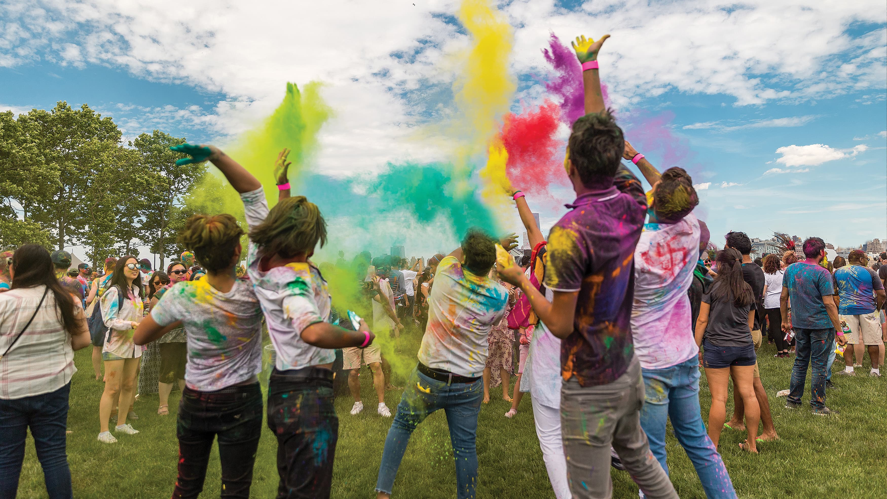 A group of people throwing colored chalk into the air at a park.