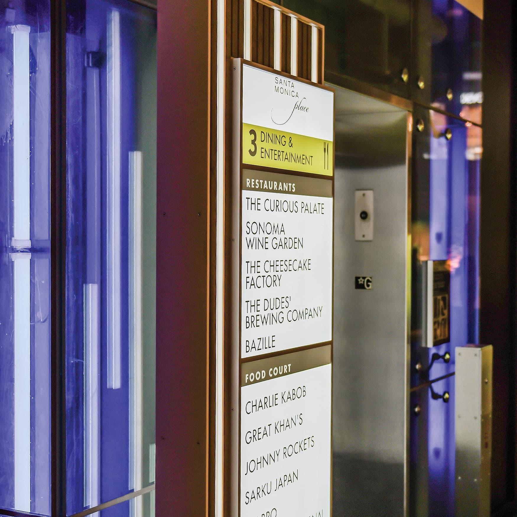 A retail directory sign illuminated at night at Santa Monica Place.