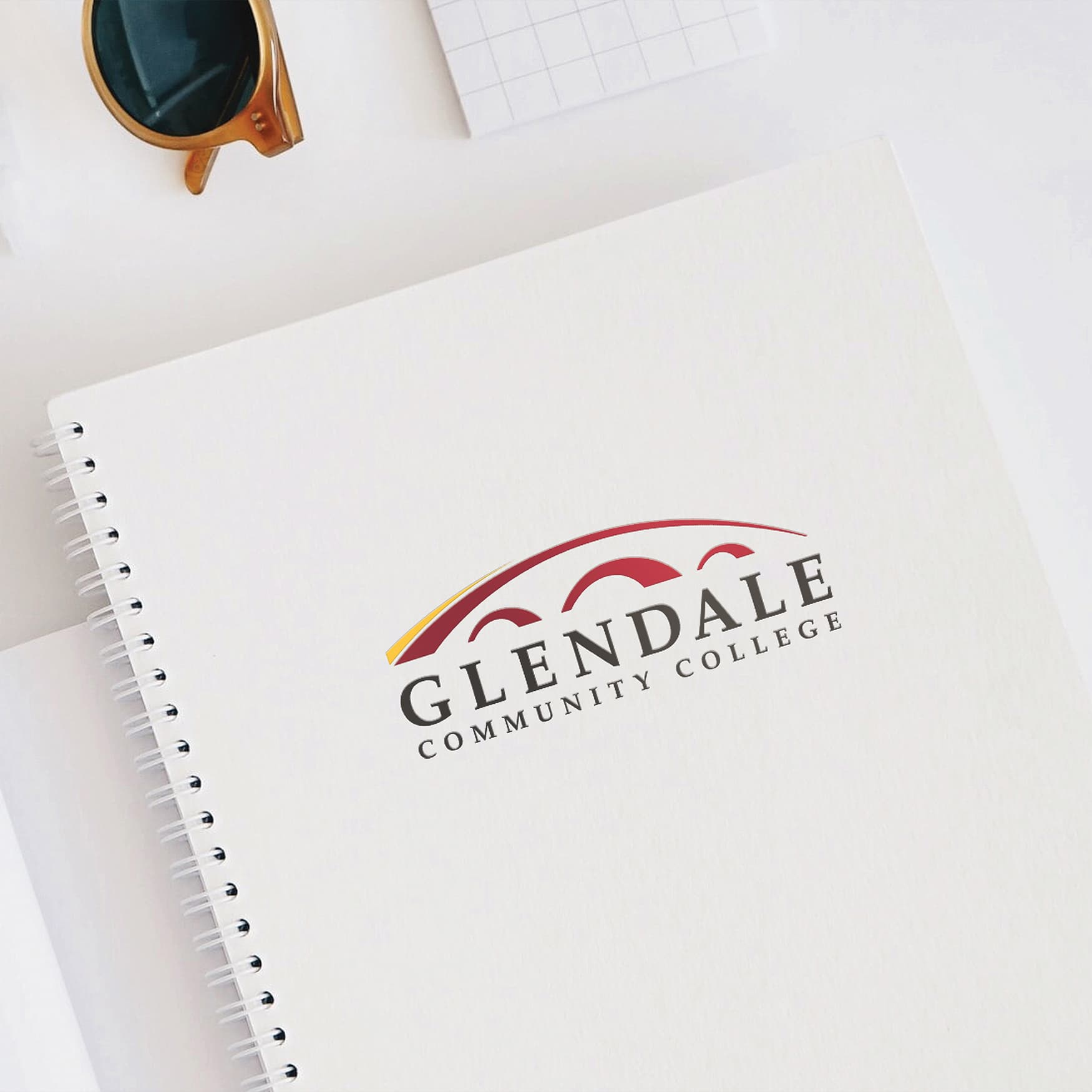 Glendale Community College logo embed on a white stationary notebook on top of a white desk.