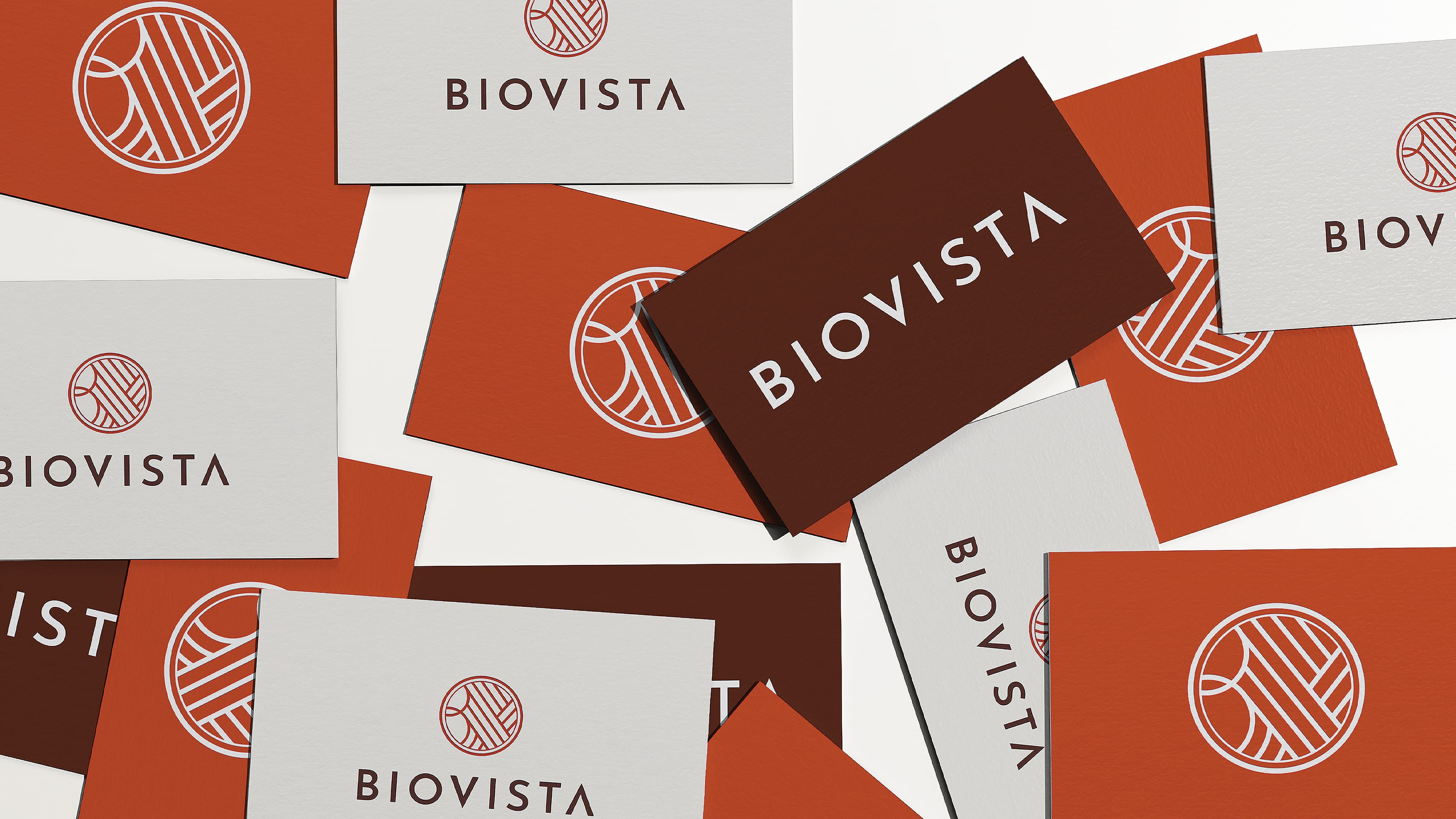 Colorful orange business cards spread across a table with the Biovista logo on them.