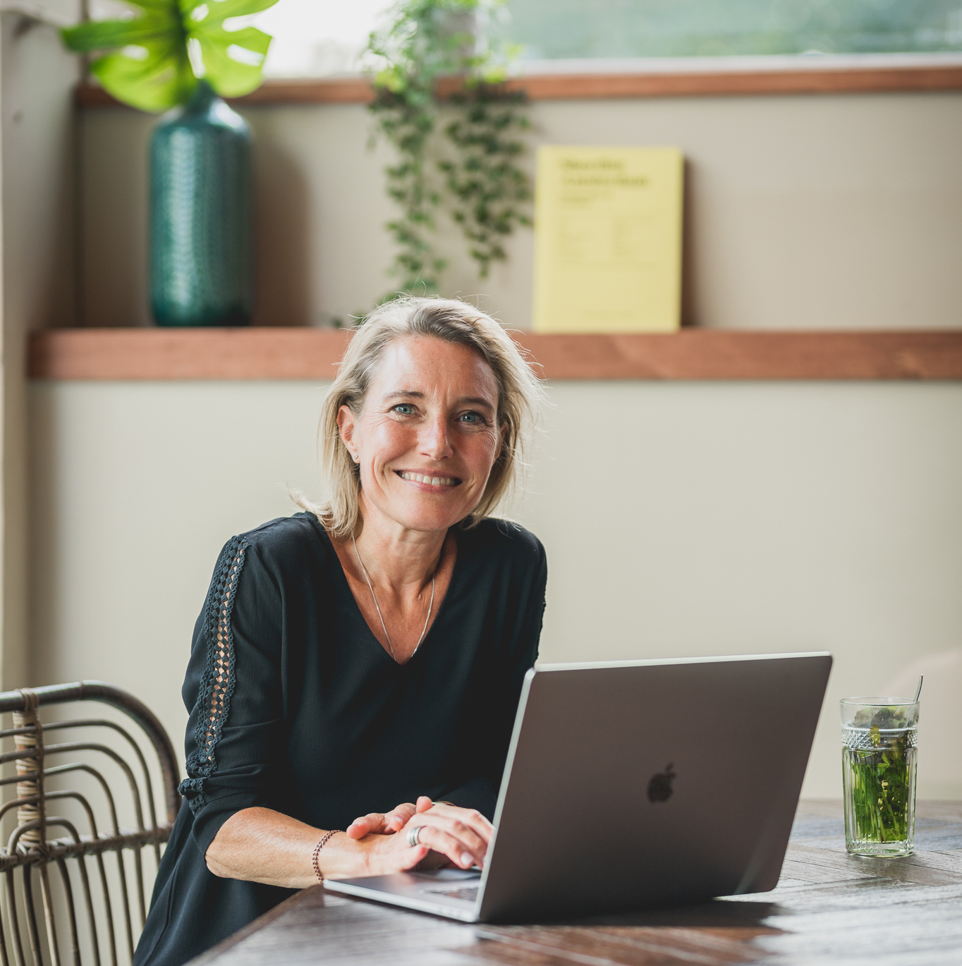 Smiling woman looking into camera with laptop in front of her