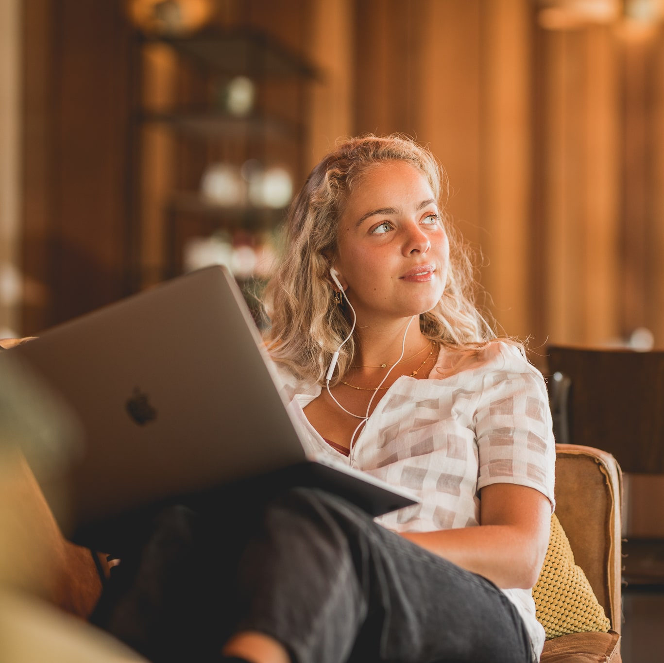 Smiling woman looking off with laptop on her lap