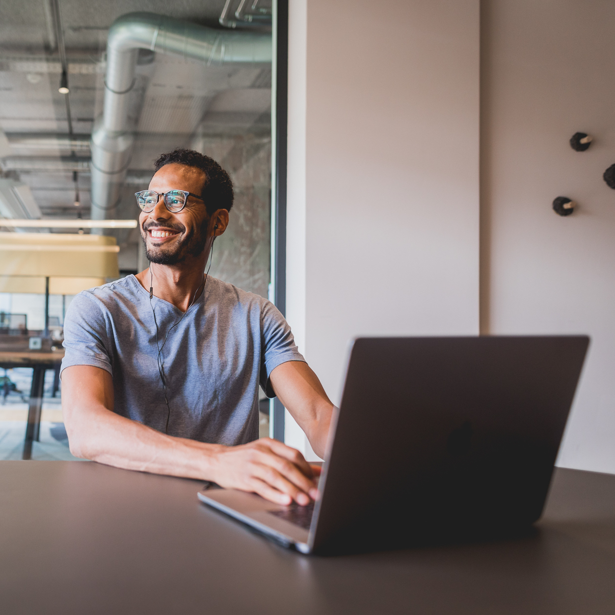 Smiling man staring off with laptop in front of him