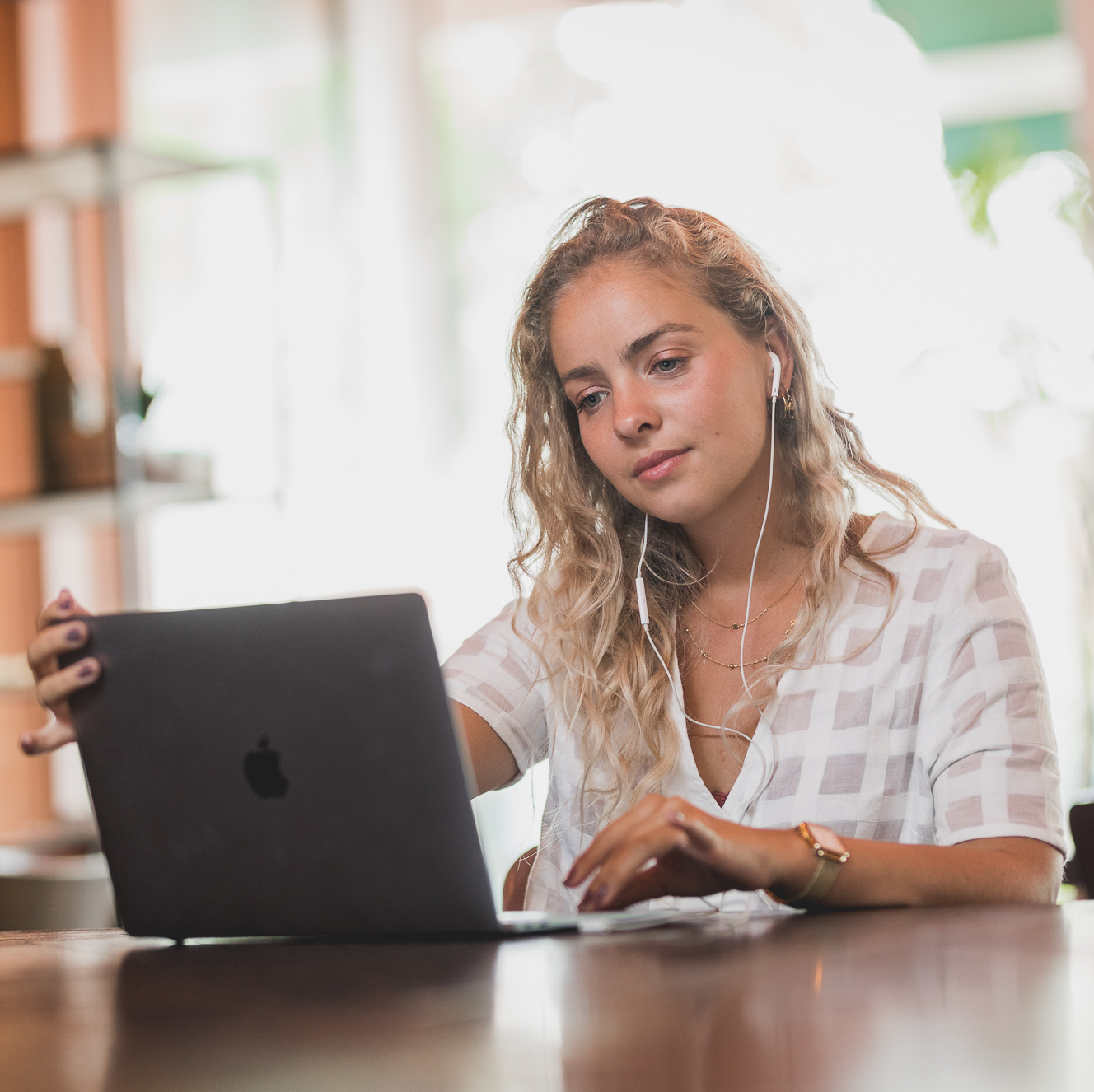 Woman looking thoughtfully at laptop in front of her