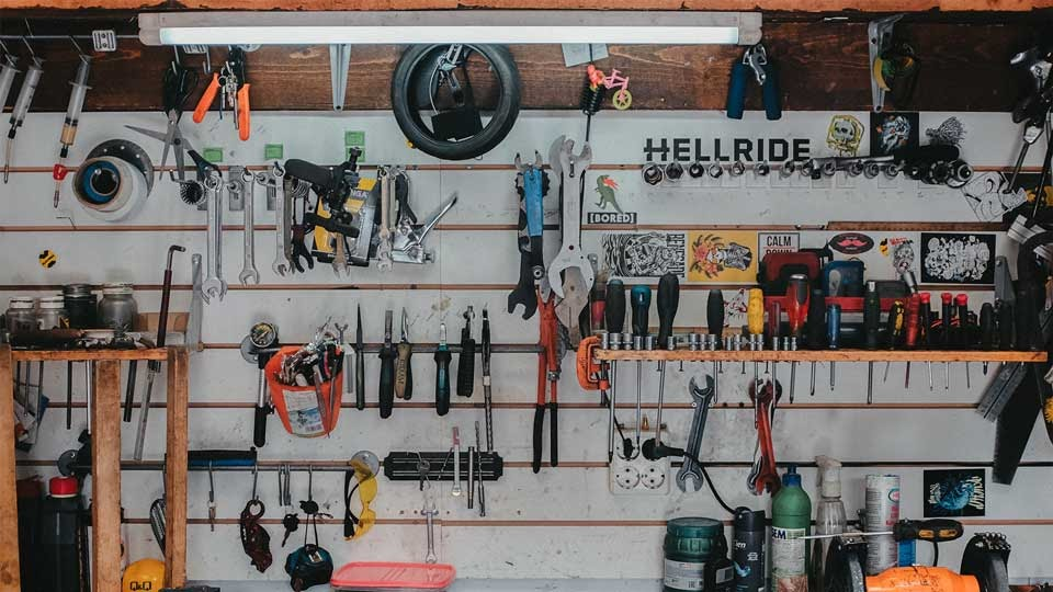 Various tools hanging on a wall in a workshop.