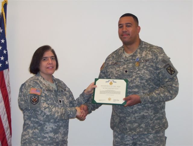 Stanley Tate in army fatigue uniform receiving an award.