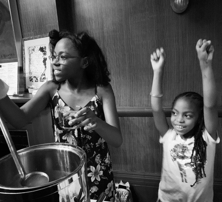 two young black girls cooking