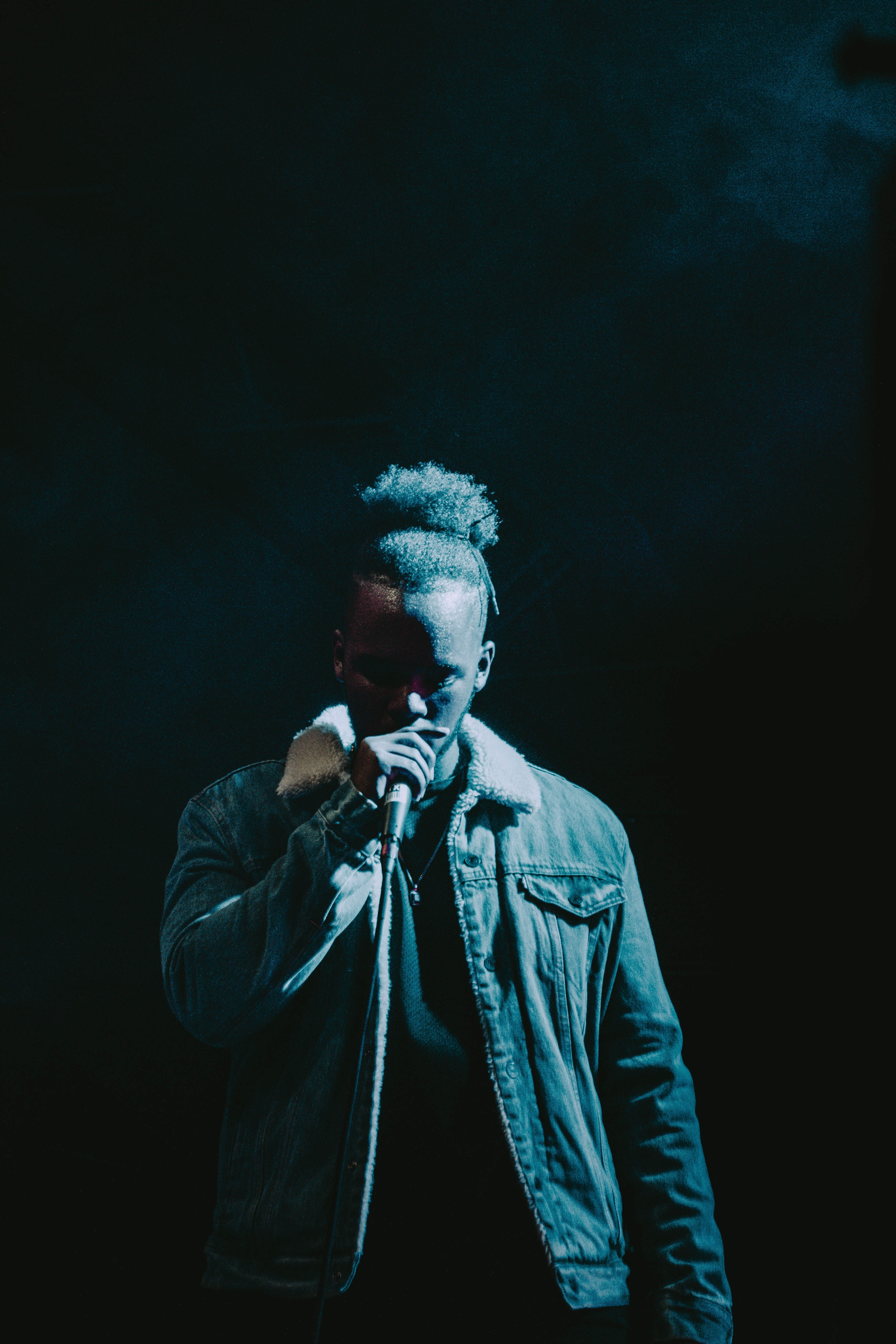 Image of a man wearing a denim jacket on stage.
