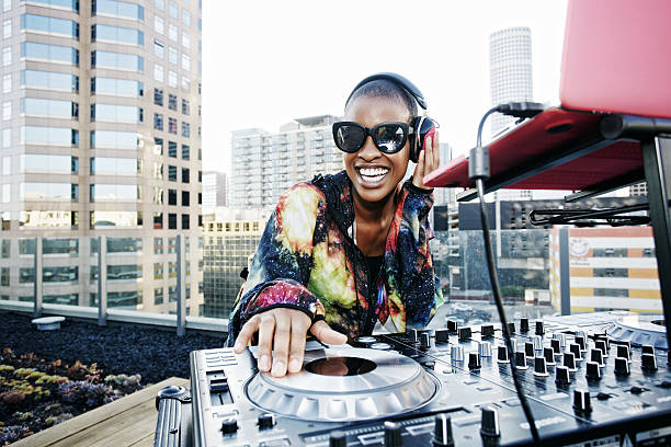 Image of a woman DJing a party on top of a high rise.