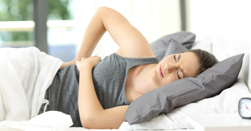 Woman in bed with her back hurting