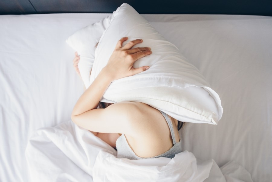 Woman covering her face with a pillow while lying on bed.