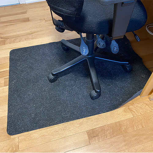 Office chair sitting on a smooth chair mat on a hardwood floor