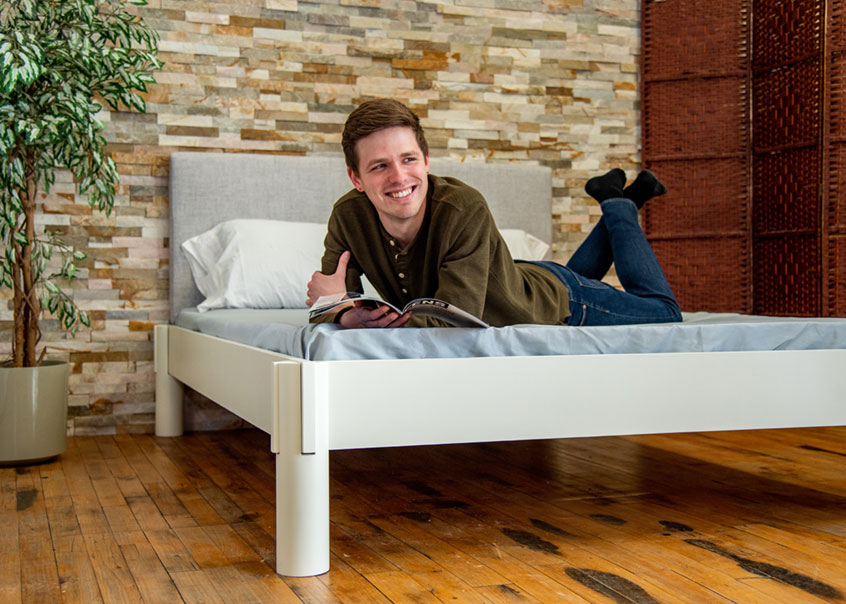 Someone lying down on Urban bed frame and smiling at camera.