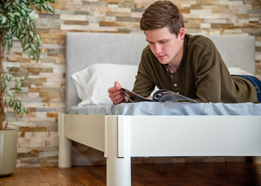 Someone reading a magazine while lying down on an Urban bed frame.