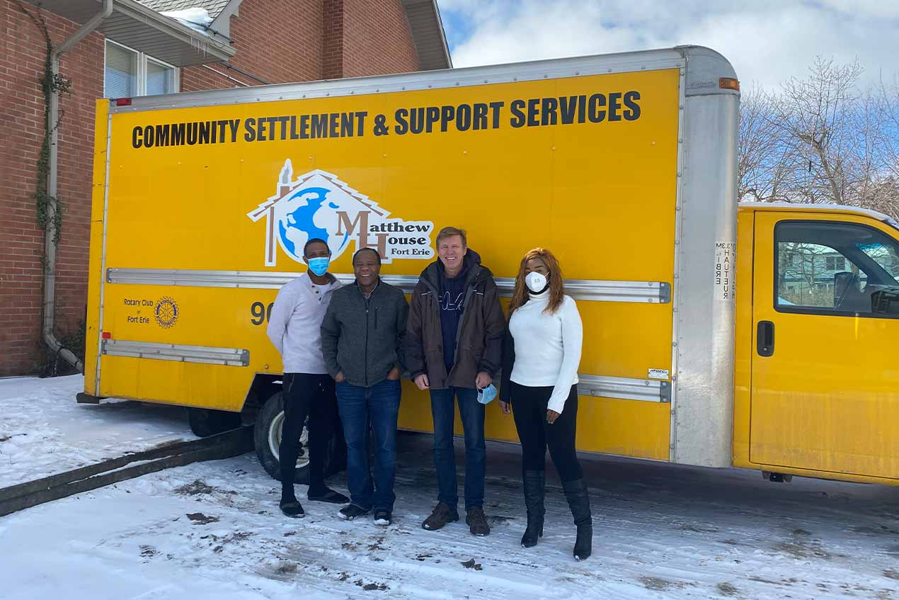 Owner of Quagga Designs and owner of Matthew House in Niagara standing in front of a Matthew House truck.