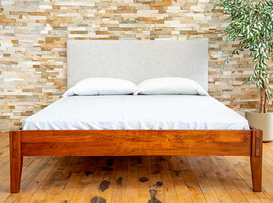 A Rustic bed frame with mattress, pillows, and headboard.