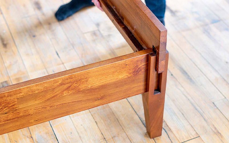 A Rustic bed frame being assembled.