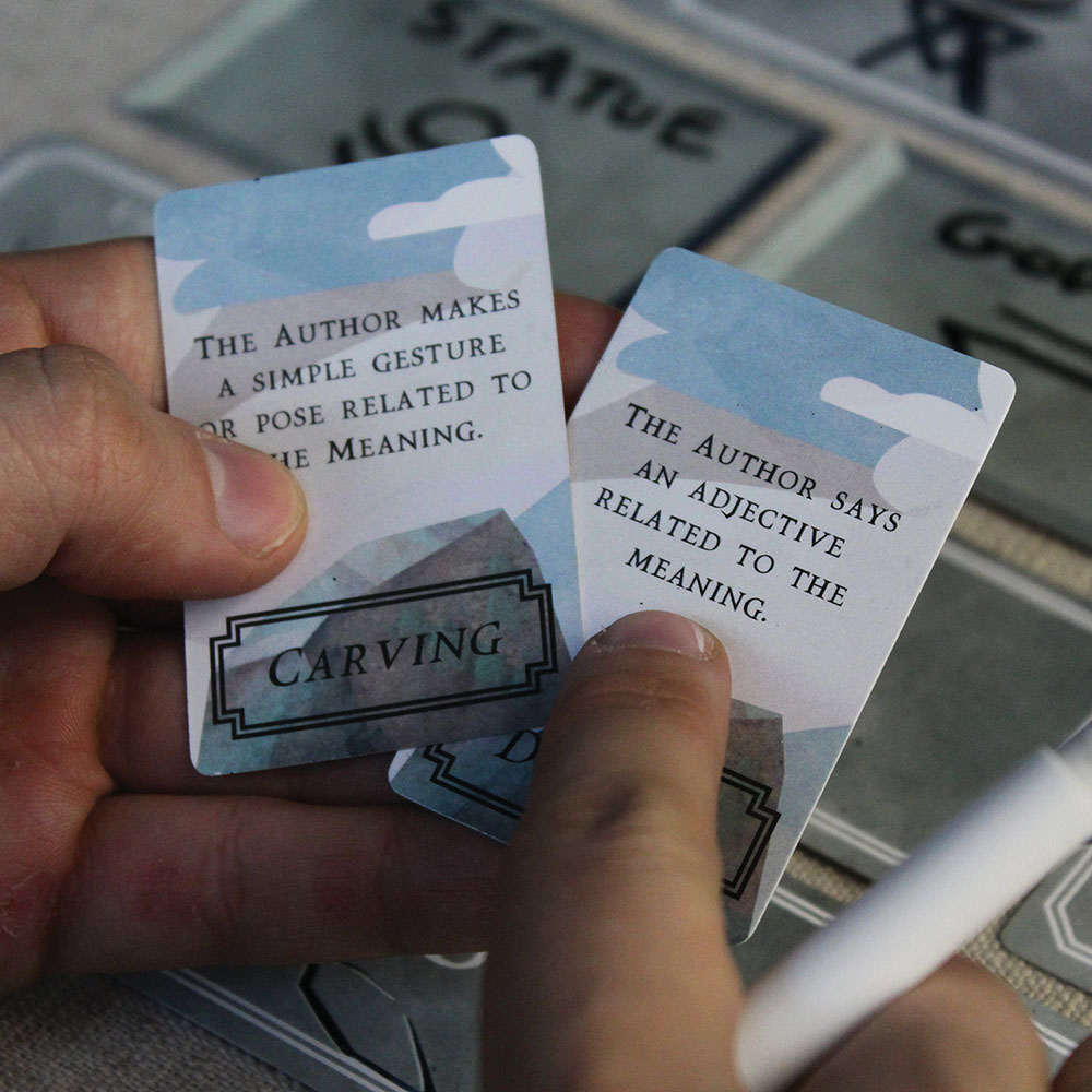 A players points at an Ability card from the board game Rosetta: The Lost Language.
