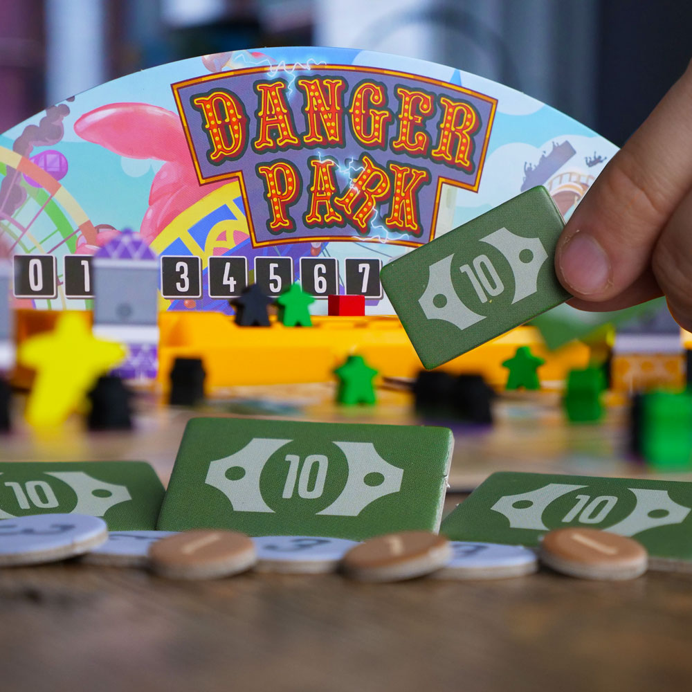 Cartoonish art of a dangerous theme park on the box of the board game Danger Park.