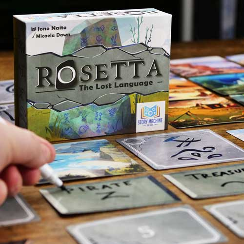 "A hand writes ""Pirate"" on a guess card in front of the box for Rosetta: The Lost Language."