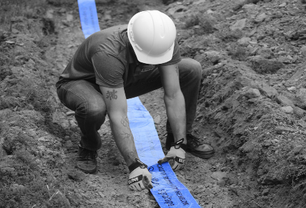 blue marker tape roll being placed in ditch