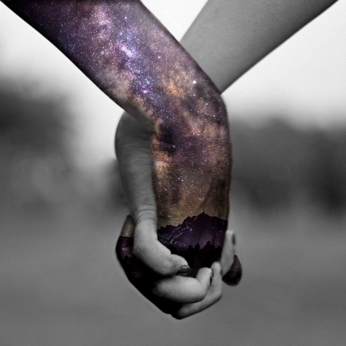Holding hands, night sky, stars, and milky way overlaid against one hand