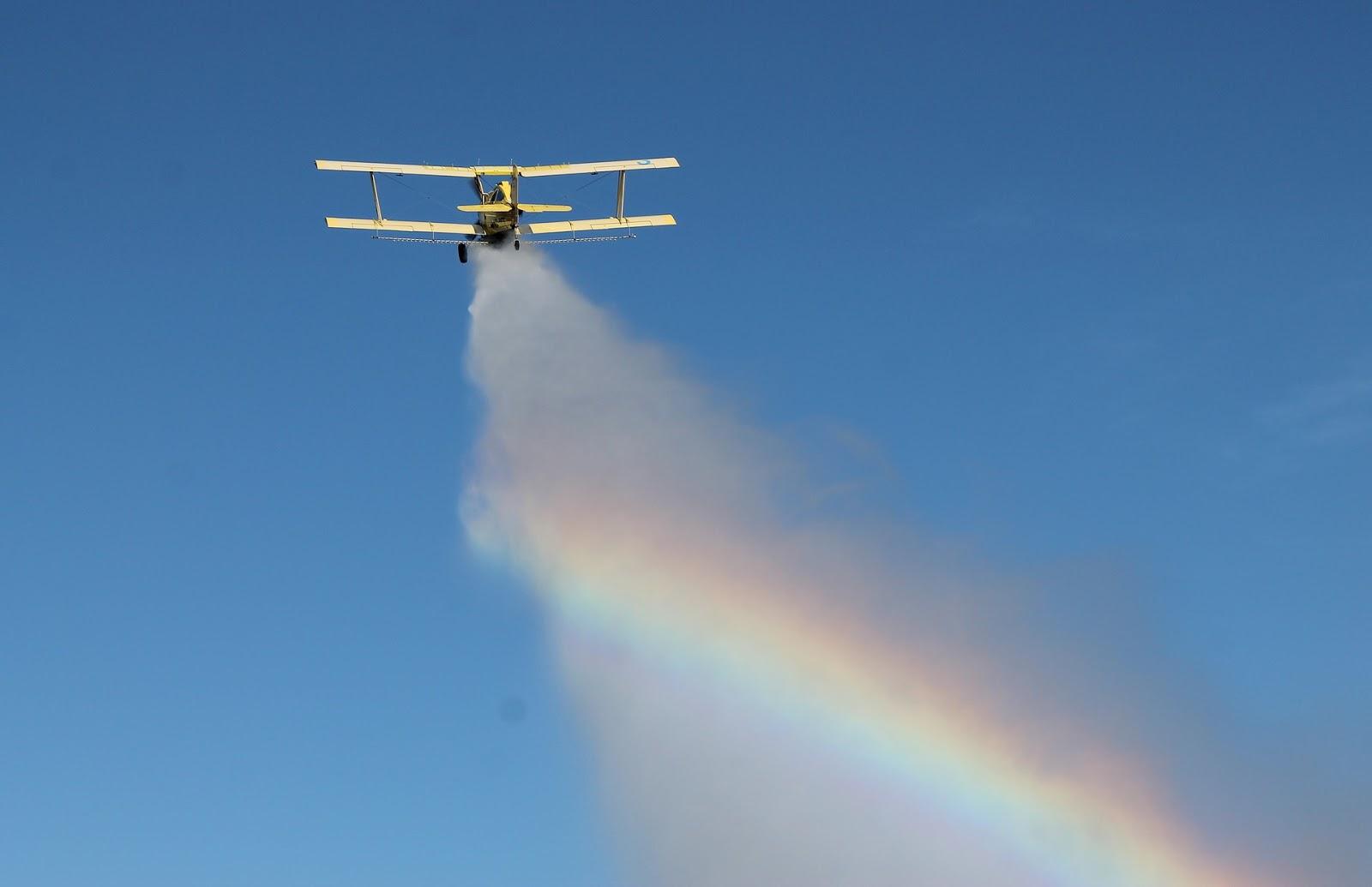 crop dusting plane spraying crops in farm