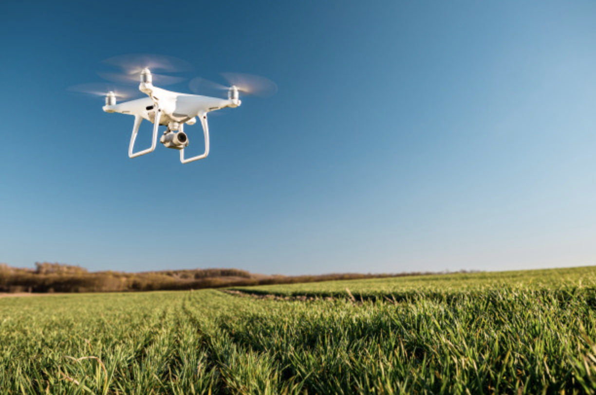 white farm drone overseeing crops