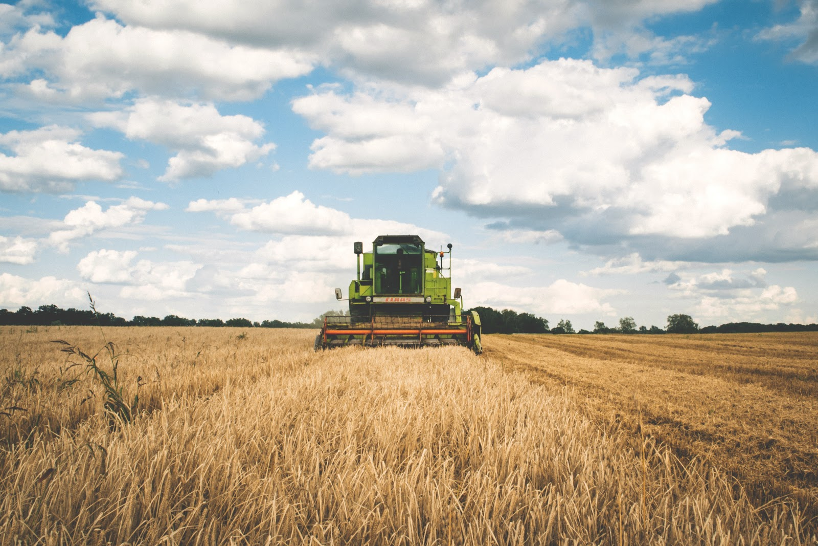 green tractor operating on a farm field